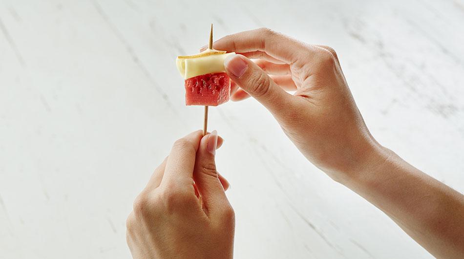 Käseigel Sunny: Wassermelonen Würfel und gerollte Fol Epi Scheibe werden auf einen Holzspieß aufgespießt.