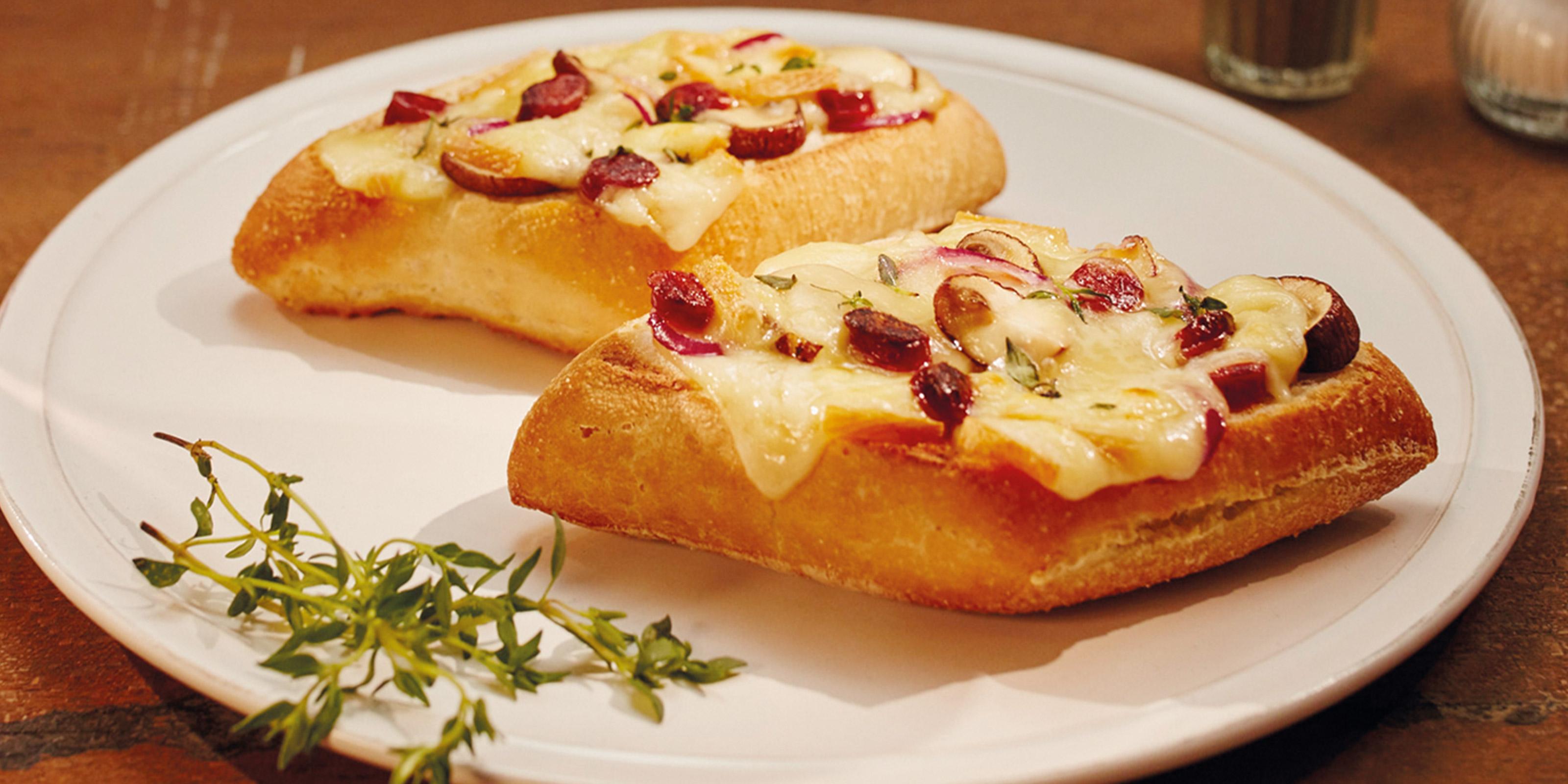 Raclette Brötchen mit aromatischem Raclette-Käse, Pilzen und Salami-Stücken.