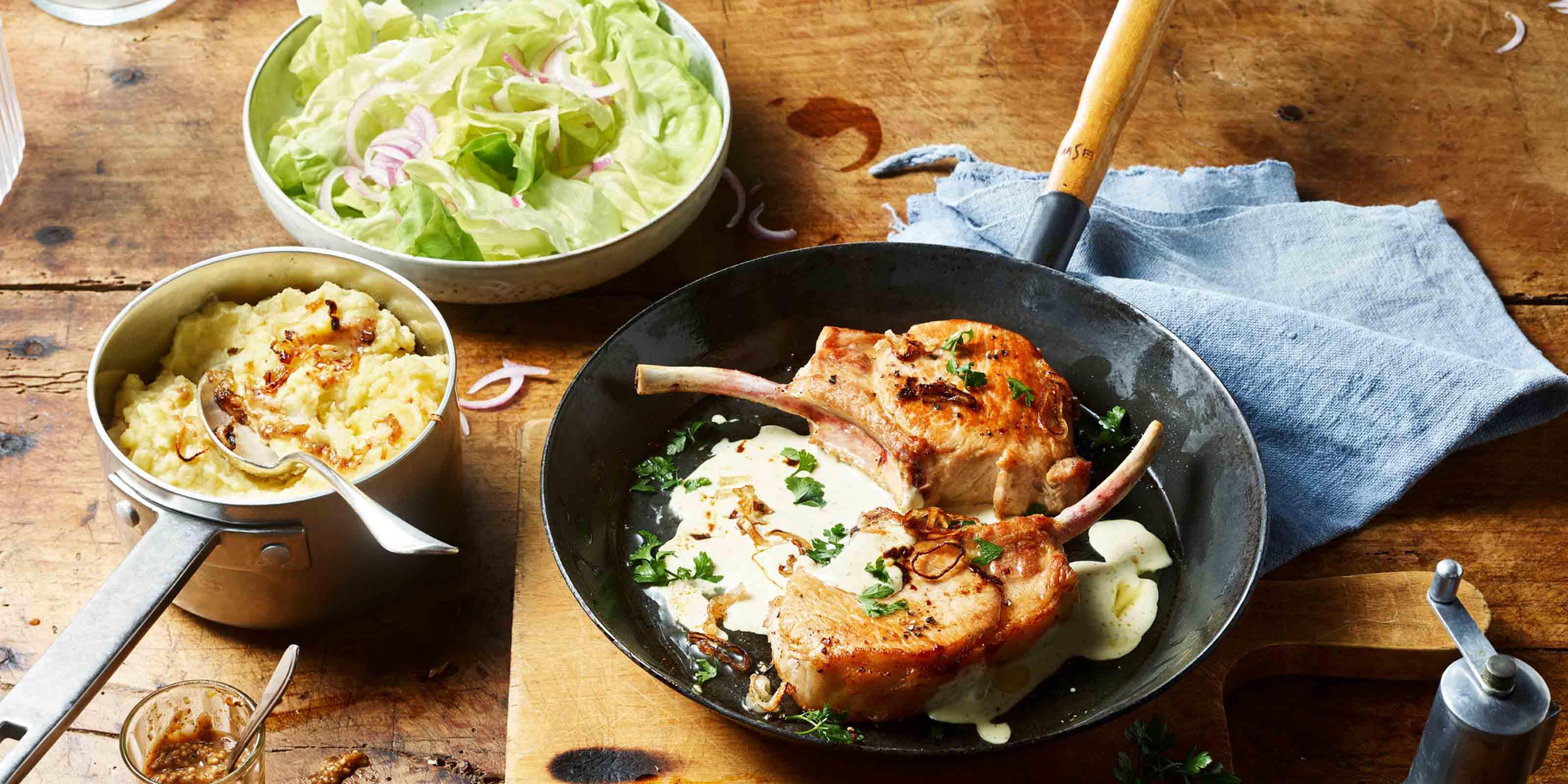 Rezept für Schweinekoteletts mit cremiger Käsesauce und Senf-Kartoffelstampf